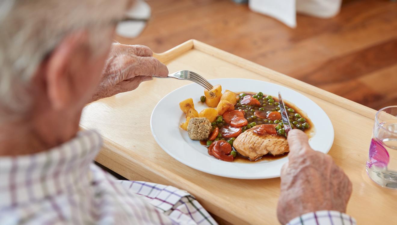 Elderly man eating meal